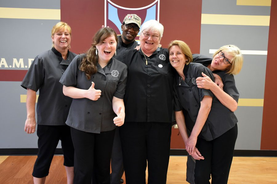 The cafeteria staff jokes around while taking their group photo for the yearbook.