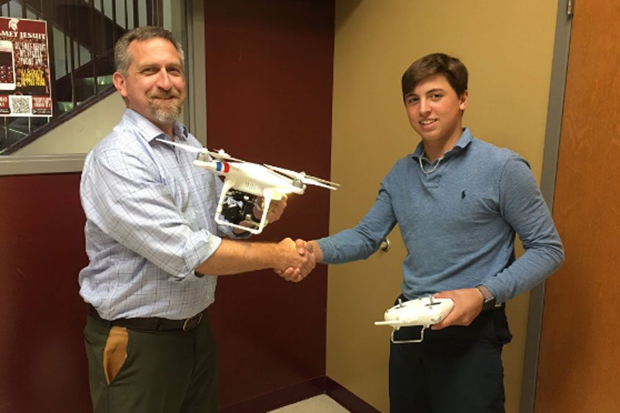 Freshman Tim Chiapel hands over the Phantom 2 drone to Principal Trevor Bonat