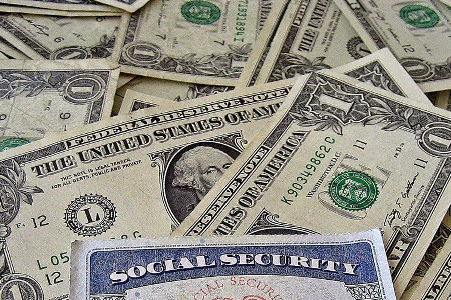 A+social+security+card+sits+upon+a+pile+of+cash.