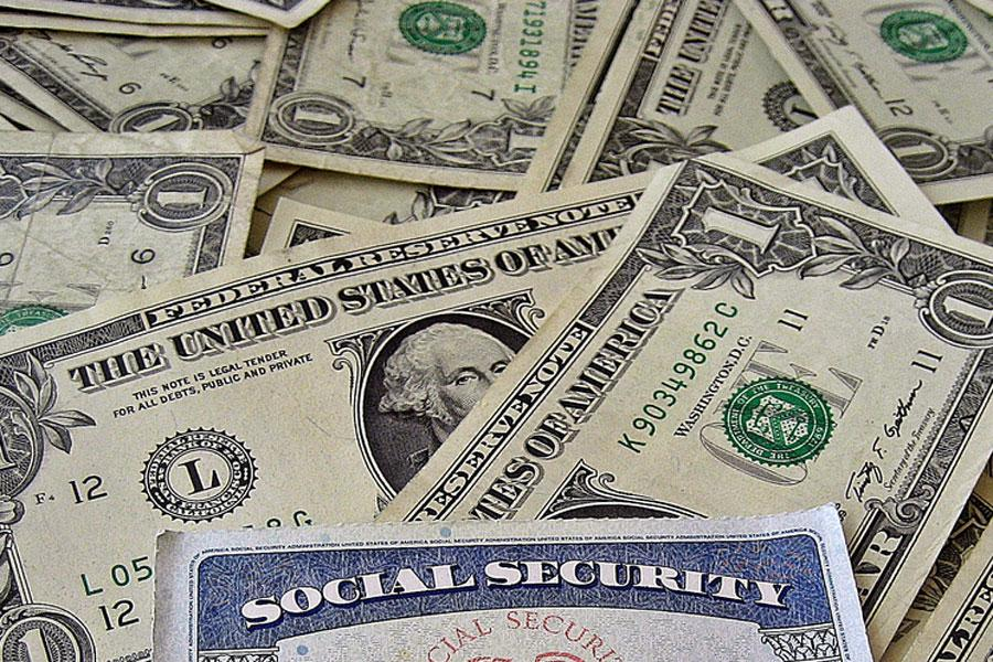 A social security card sits upon a pile of cash.