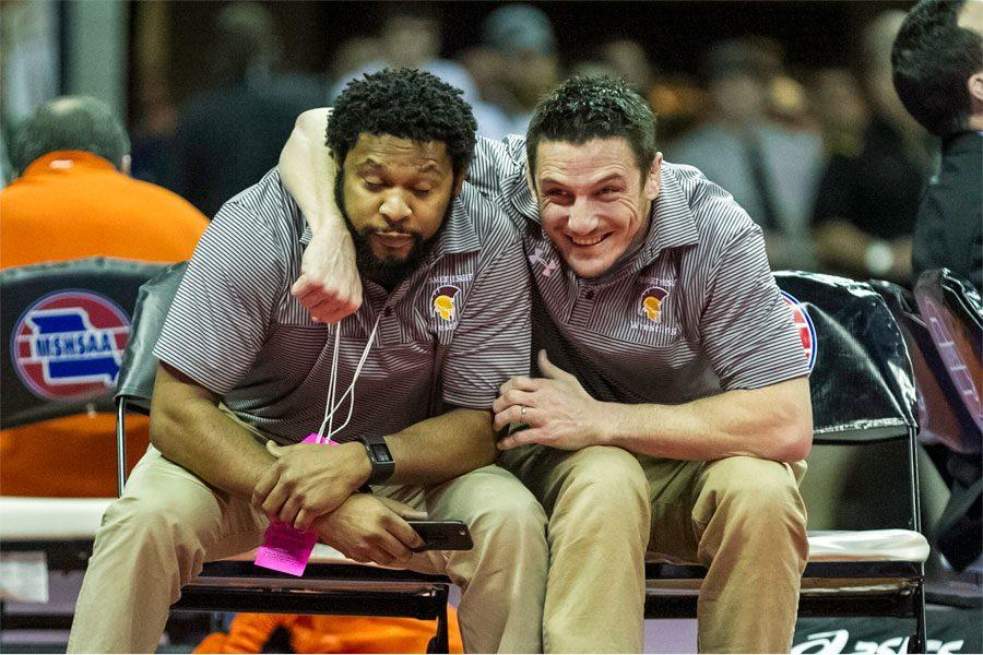 Head wrestling coach Colby Robinson celebrates with assistant coach Anton Prater after sophomore wrestler Corey Peterson finished second in the state tournament Feb 17.