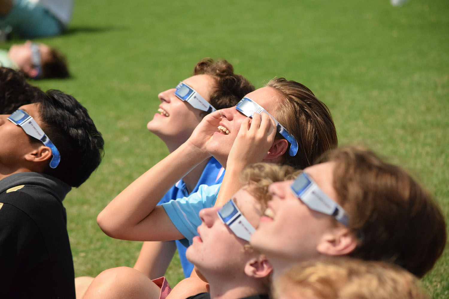 Looking up at the sun, Desmet students watch the moon cover the sun.