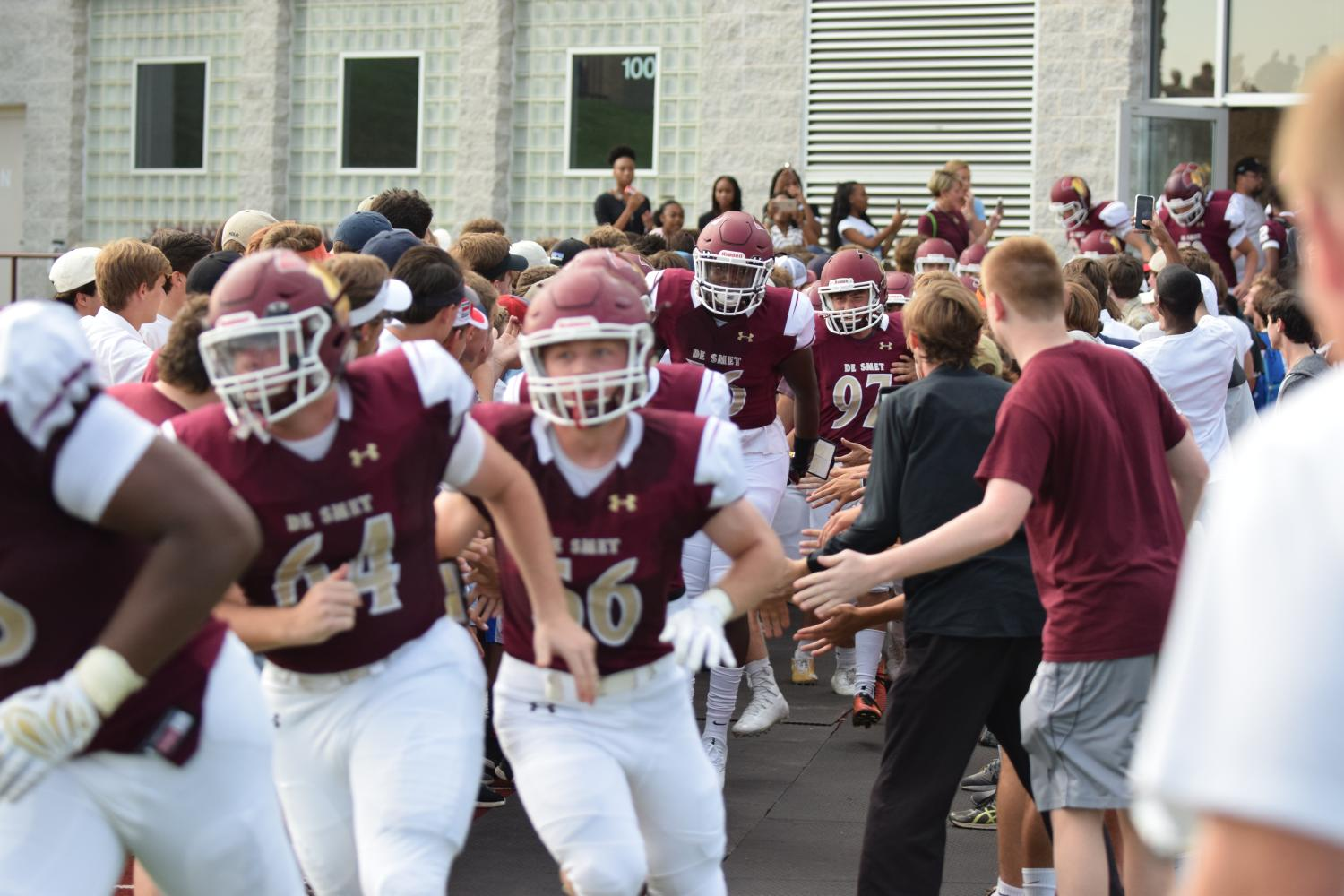 The De Smet football team rushes through the crowd of fans to enter the game.