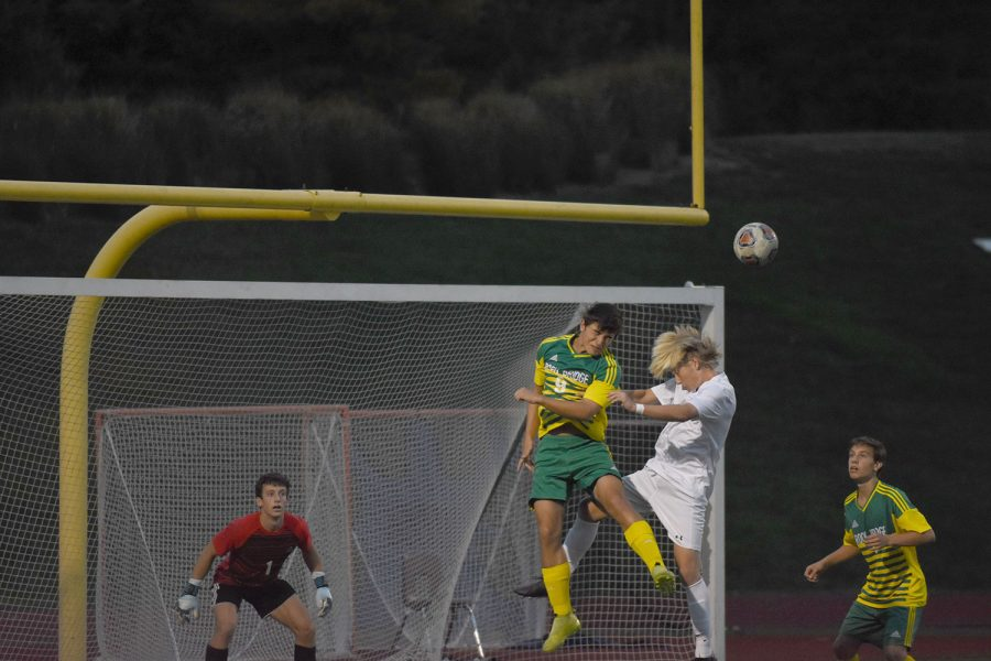 The boys come out firing as Junior Forward Carsen King battles for position on a corner kick ball early in the first half against Rock Bridge.