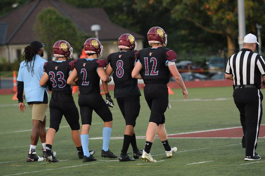 The+captains+walk+onto+the+center+of+the+field%2C+locking+arms%2C+to+determine+the+coin+toss.