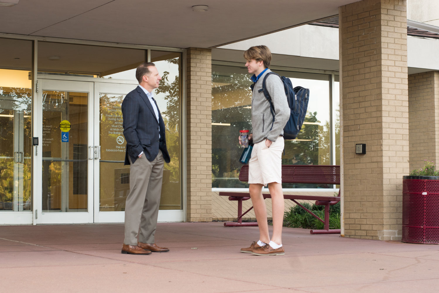 "Dr. Corey Quinn greets senior Jay Dolan before school. ""I'll say it till I'm blue in the face, the best part of my day every day is standing out in front of Emerson and saying hi to you guys,"" Quinn said. ""I just wish I had more time to be in your presence. It's the best part of my job."""