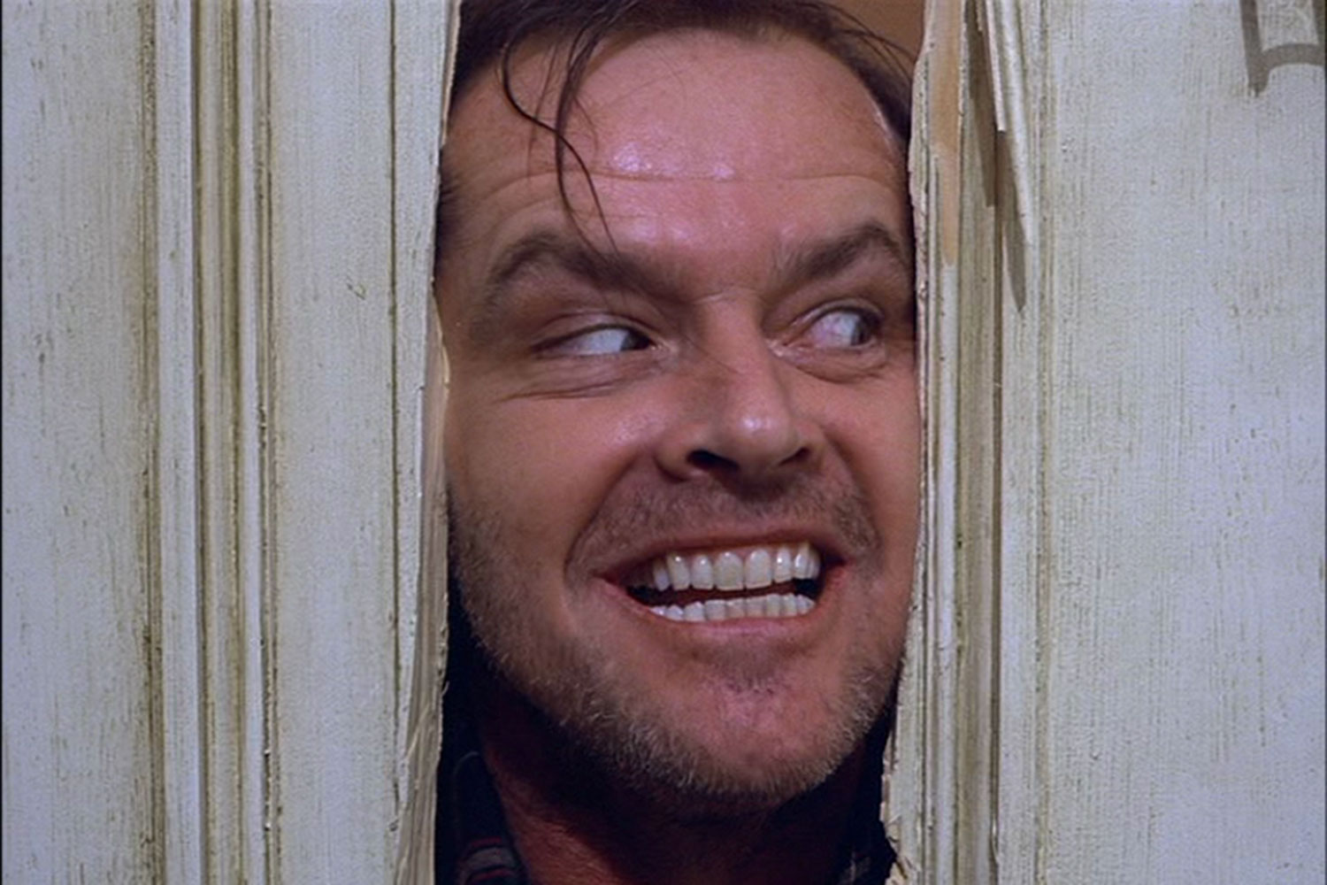 Jack Nicholson bursts through the door, trying to break in.