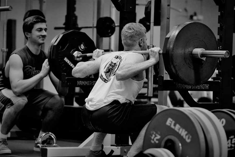 Senior+Jack+Combs+squats+315+pounds+while+senior+Troy+Schneider+spots+him.