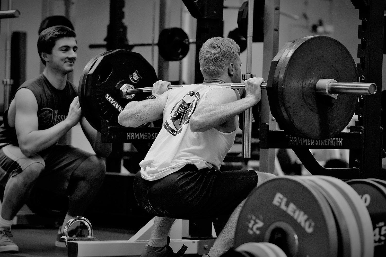 Senior Jack Combs squats 315 pounds while senior Troy Schneider spots him.