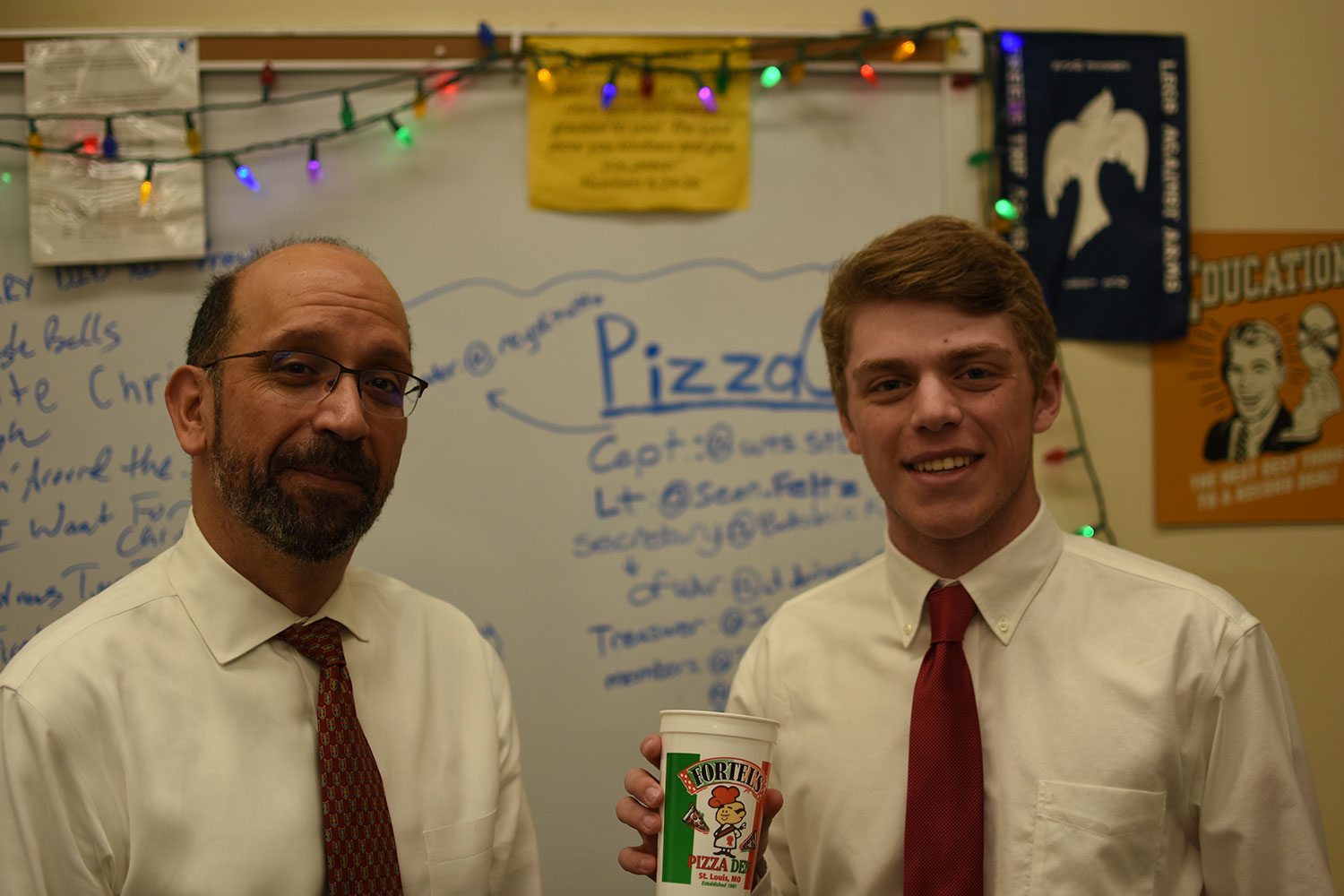 Senior Tyler Dawson and club moderator Ray Sherrock pose with a Fortel's Pizza cup.