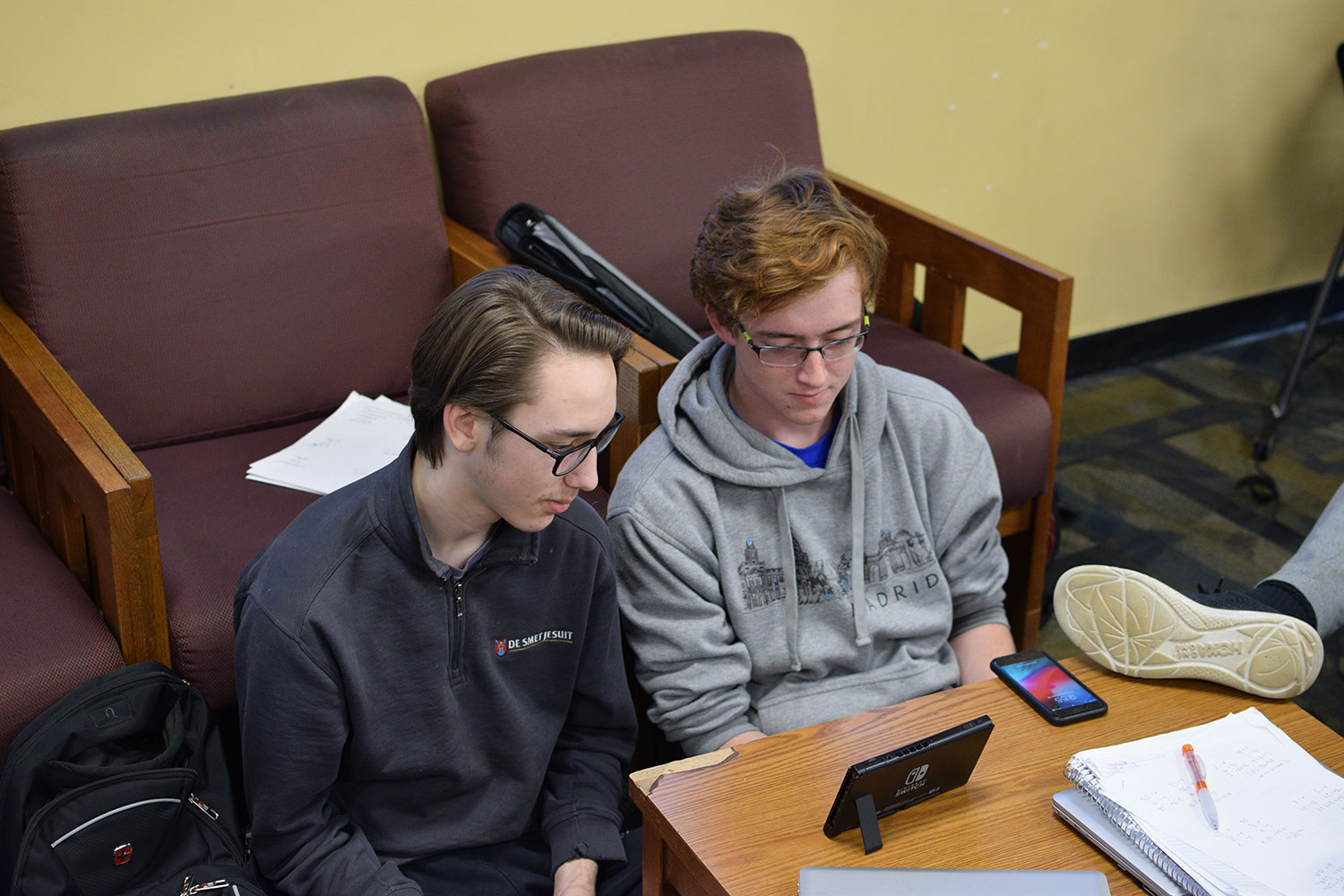 Taking a break from studying two students relax by playing the Nintendo Switch.