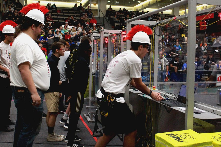 At the start of the match, Senior Jacob Deighton and Coach Anthony Strawhun prepare to take control of the robot. Matches start out with a period of time in which robots are required to be autonomous. Following this, a human driver takes control.
