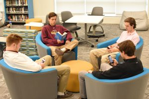 Students sit in the innovation center on social media while one reads the Gettysburg Address.