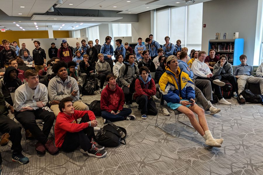 Students watch senior Connor Blom as he plays Fortnite, later Blom goes on to earn a Victory Royale!