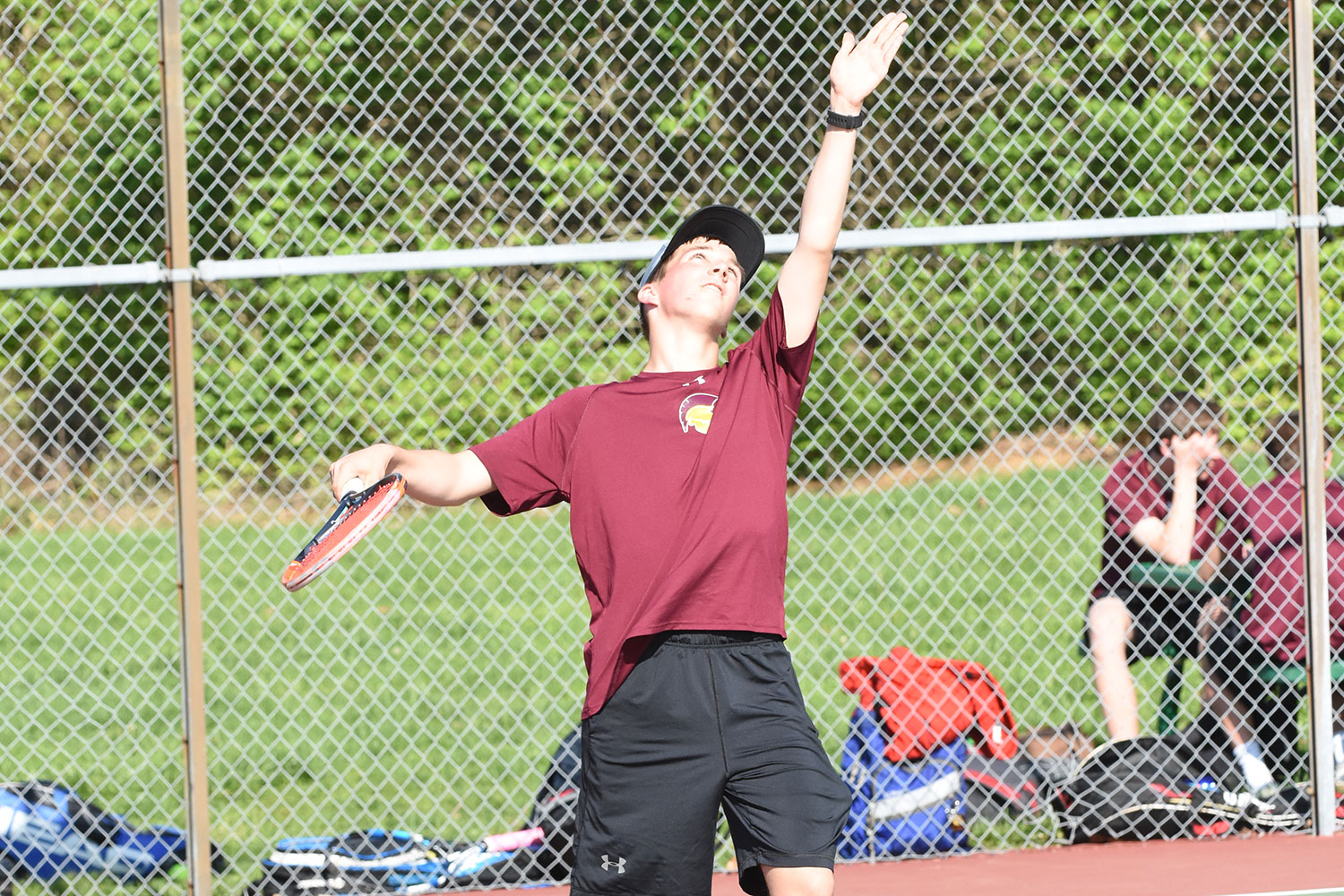 Senior tennis star Matthew Dubuque throws up the ball and winds up his racket to serve the ball.
