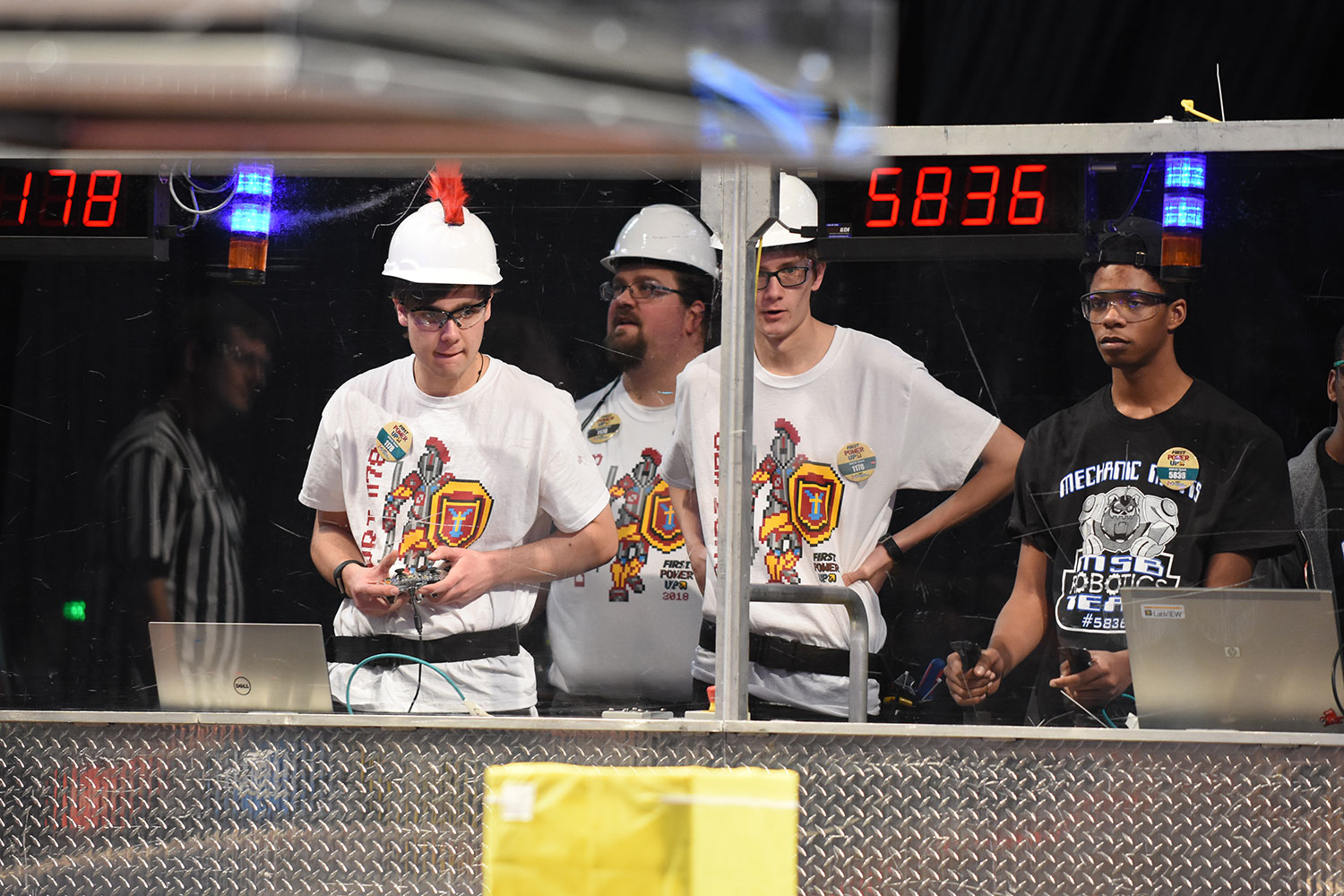 senior Jacob Deighton controls his robot as the rest of the team looks on.