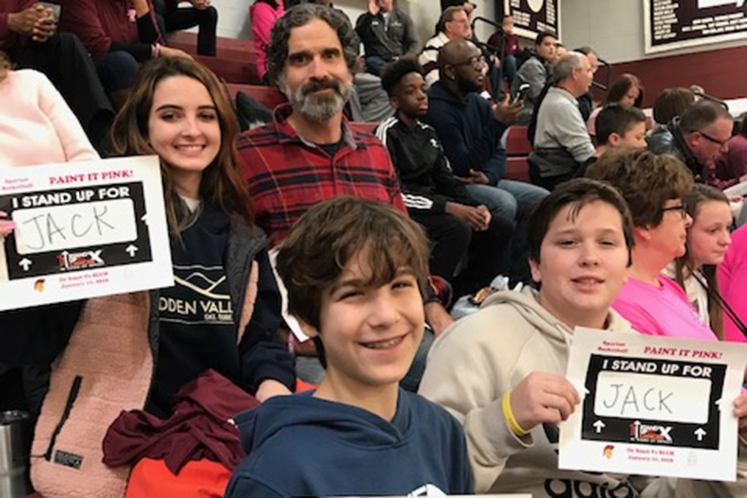 Jack's dad, sister, brother and his friend support Jack at the Paint it Pink basketball game.