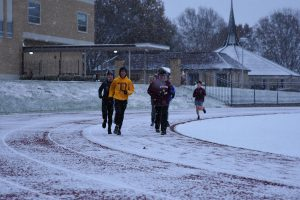 A group of runners led by Assistant Varisty Track Coach teacher Adam Boehm, run on a snowy day.