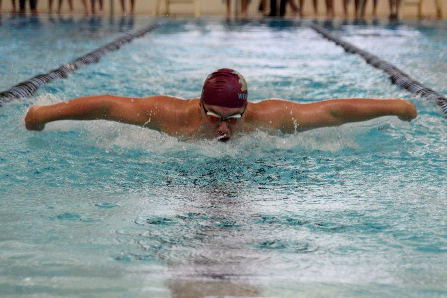 Junior Liam Weishaar takes part in the 100 meter butterfly race.