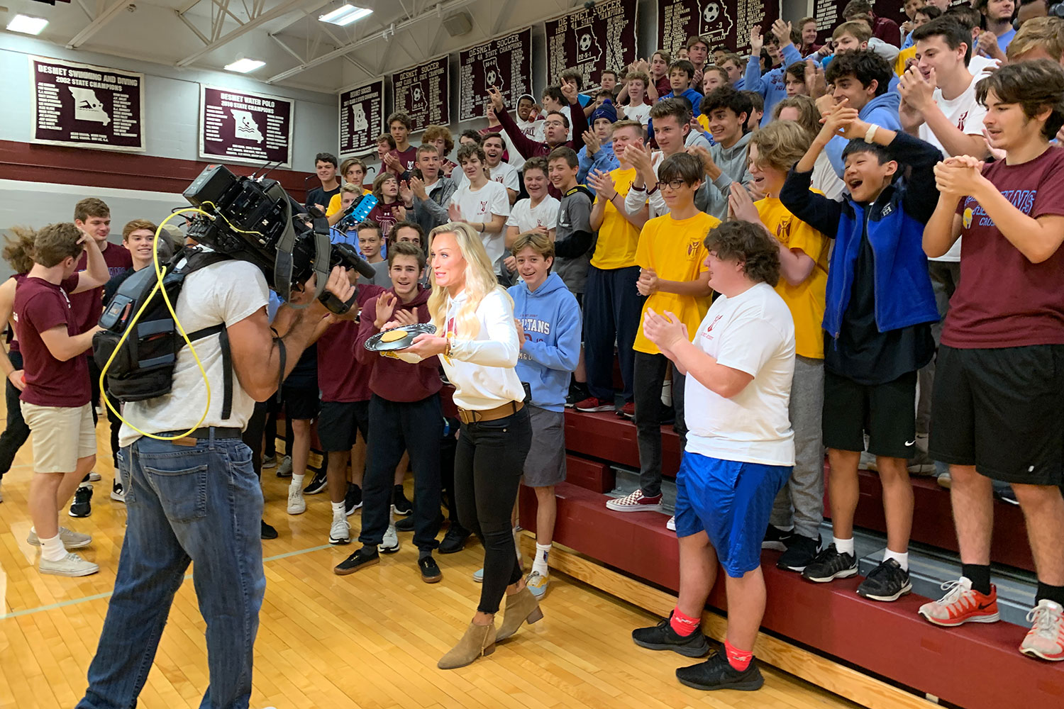 A crowd of students gathers around Fox 2 reporter Katherine Hessel during a live shot Friday morning as part of the Pep Zone. The program featured De Smet in their Friday football coverage.