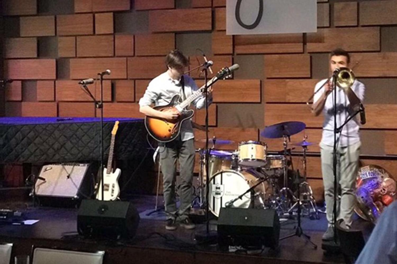 Aidan Bartholet tunes his guitar before a performance.