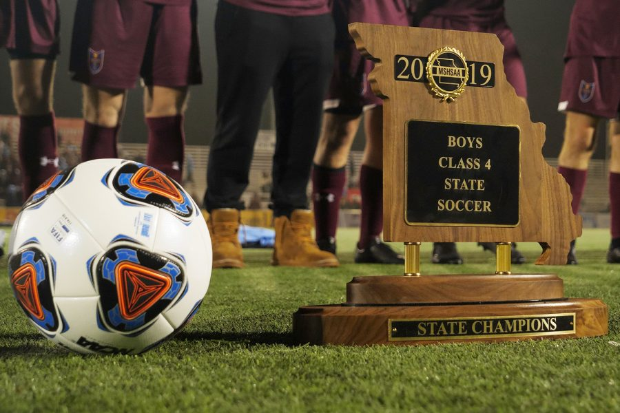 Boys stand behind MSHSAA Class 4 State Soccer Trophy and gameball during post-game ceremony.