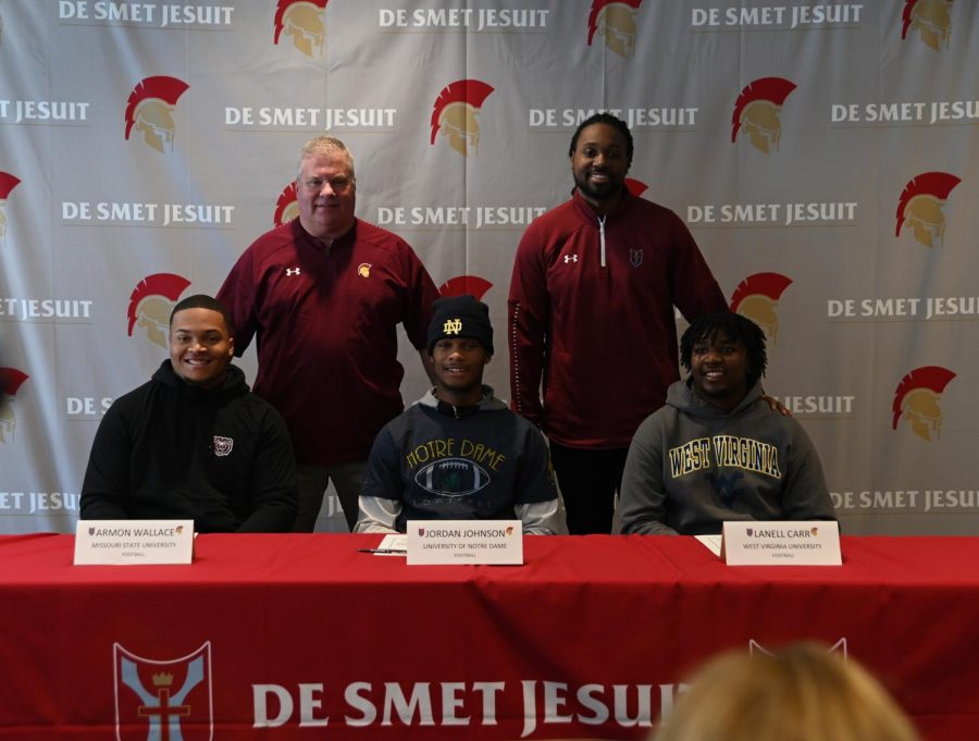 Armon+Wallace%2C+Jordan+Johnson%2C+and+Lanell+Carr+pose+with+Athletic+Director+John+Pukala+and+Head+Football+Coach+Robert+Steeples+for+a+photo+before+the+signing+ceremony+on+Dec.+18+in+the+Innovation+Center.