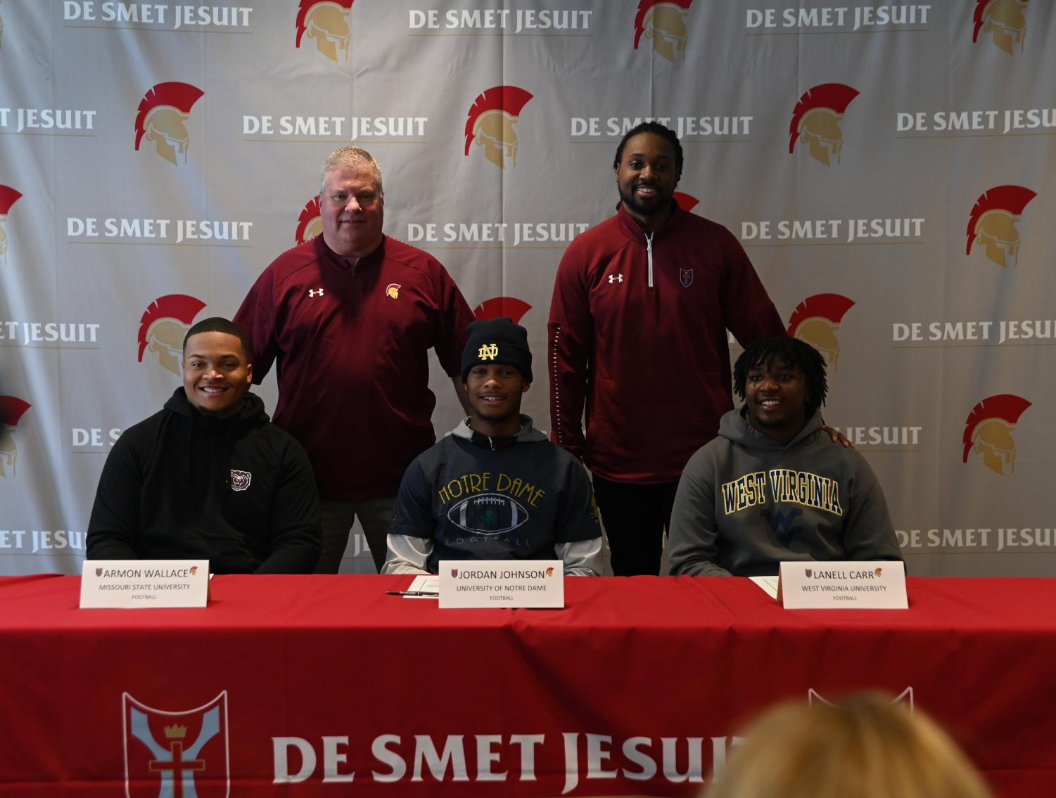 Armon Wallace, Jordan Johnson, and Lanell Carr pose with Athletic Director John Pukala and Head Football Coach Robert Steeples for a photo before the signing ceremony on Dec. 18 in the Innovation Center.