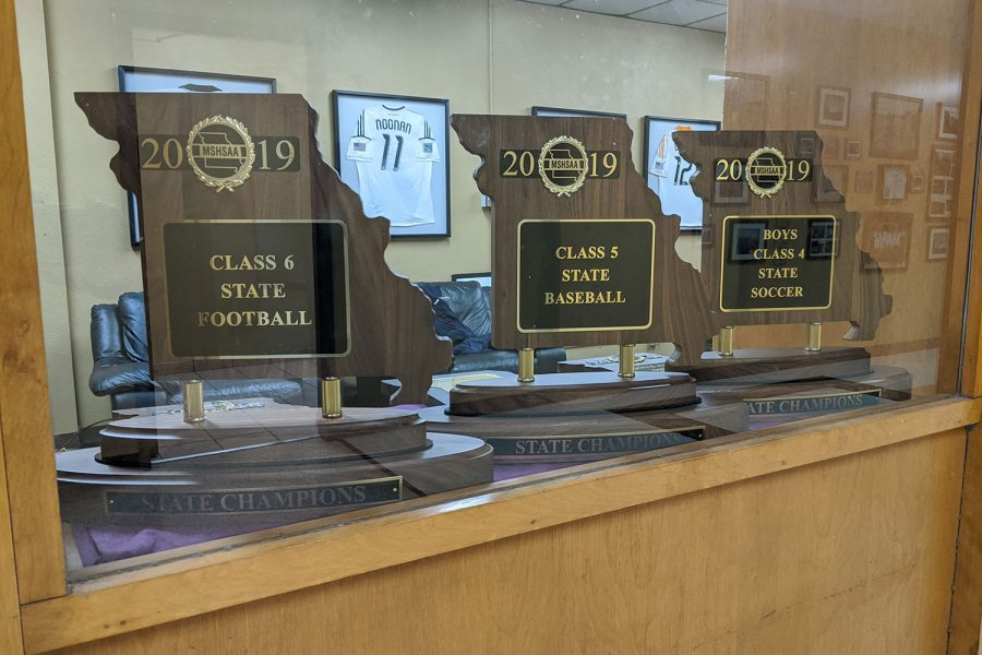 The+three+2019+state+championship+trophies+sit+on+display+in+the+athletic+office.++An+all-school+assembly+will+honor+the+three+teams+Jan.+10.