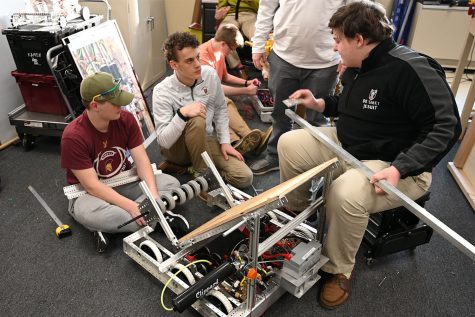 Sophomore Austin York, junior Thomas Schuster and senior Ryan Sei prepare to install the climbing mechanism on the robot.