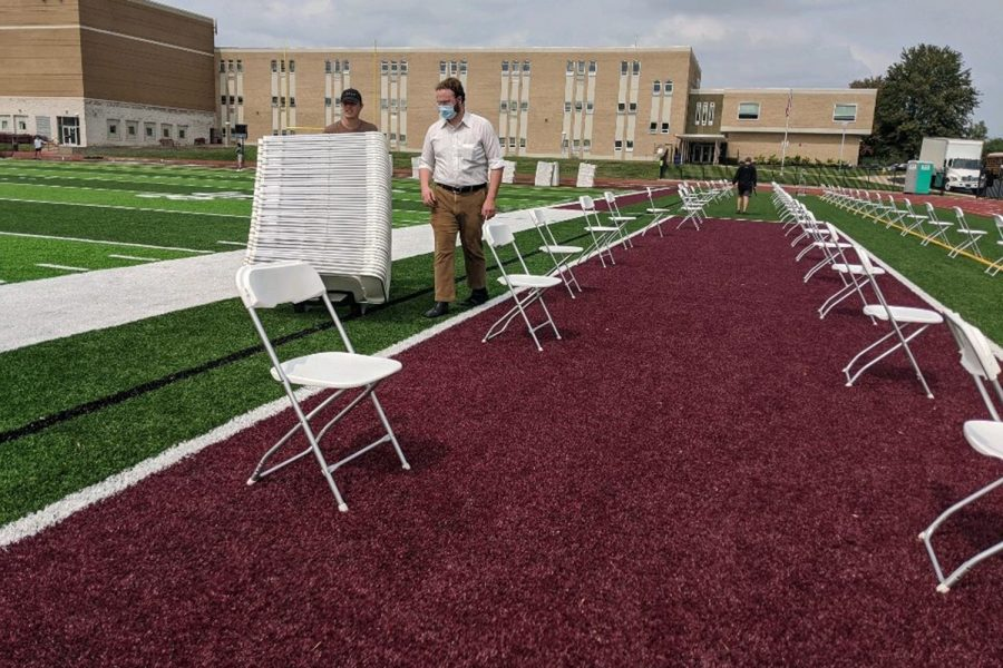Workers from the Aries company prepare to set up 800 chairs 6 feet apart on the turf.
