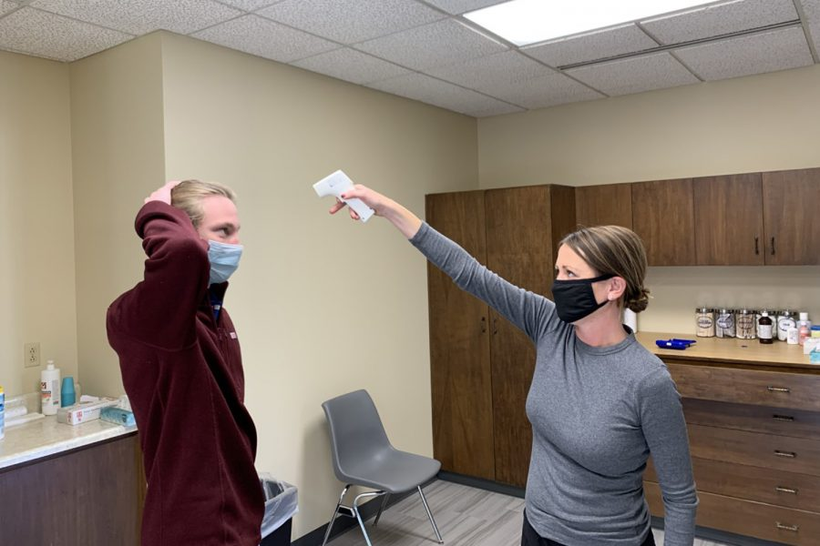 Nurse Molly Deveruex tests Senior Ryan Flavin's temperature.