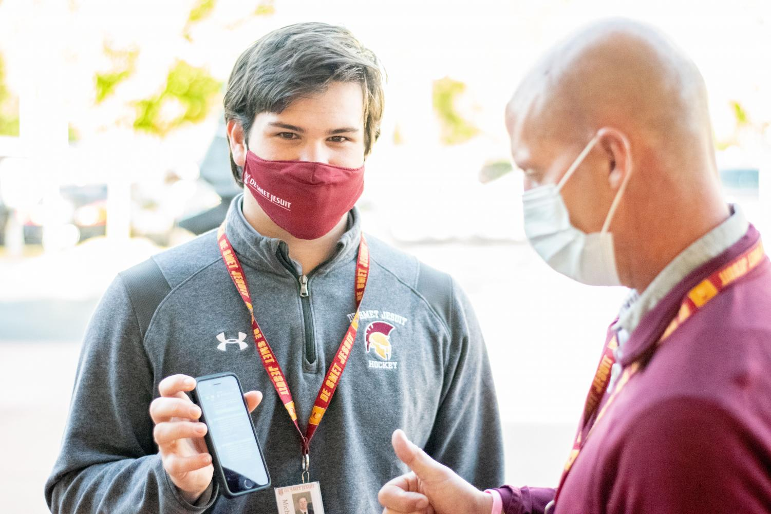 Mr. Degreeff checks Senior Mike Mattern health app to give him the okay to enter school outside of the Emerson Lobby.