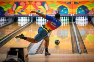 Senior Justin Kennedy bowls a strike during a bowling game.