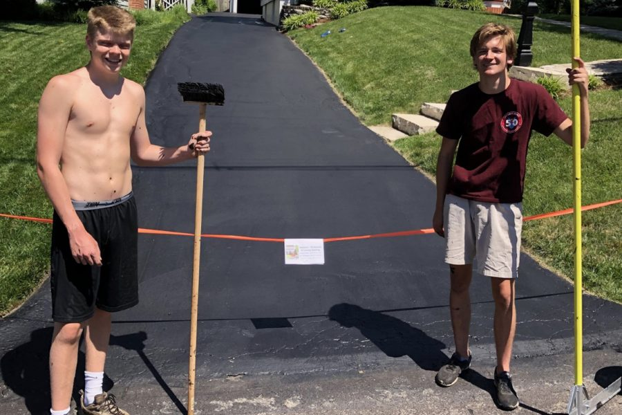 Seniors Michael Dolan and Jack Venneman pose for a photo after sealing their first driveway over the summer.