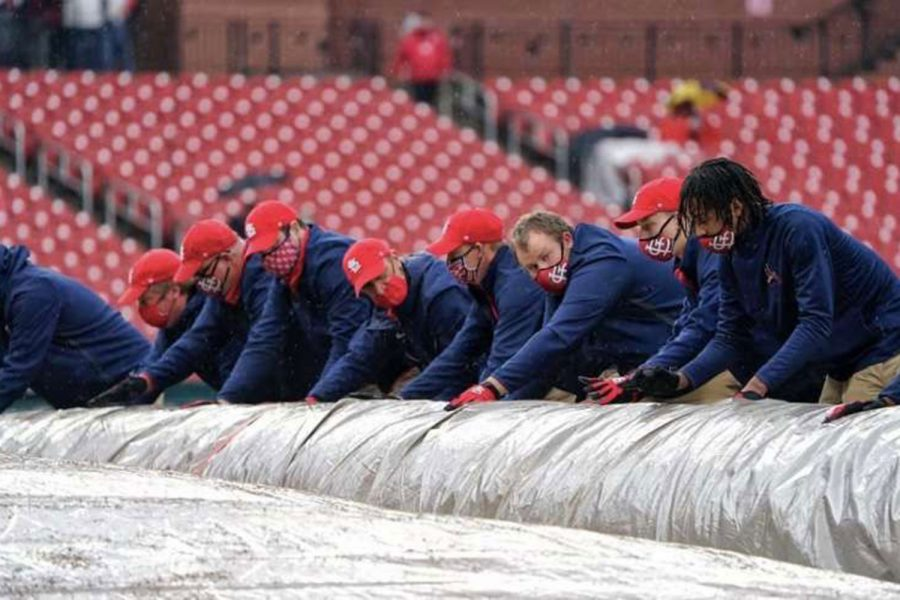 Ethan Weishaar (second from right) helps roll up the tarp after a rain delay at Busch Stadium. The sophomore is the youngest member of the Cardinals grounds crew.