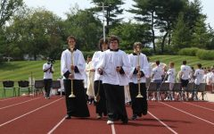 Altar servers Tommy Hashbarger, Aiden Madigan, Daniel Dowell, and Jack Stanley lead the clergy out of the stadium to end the Mass of the Holy Spirit.