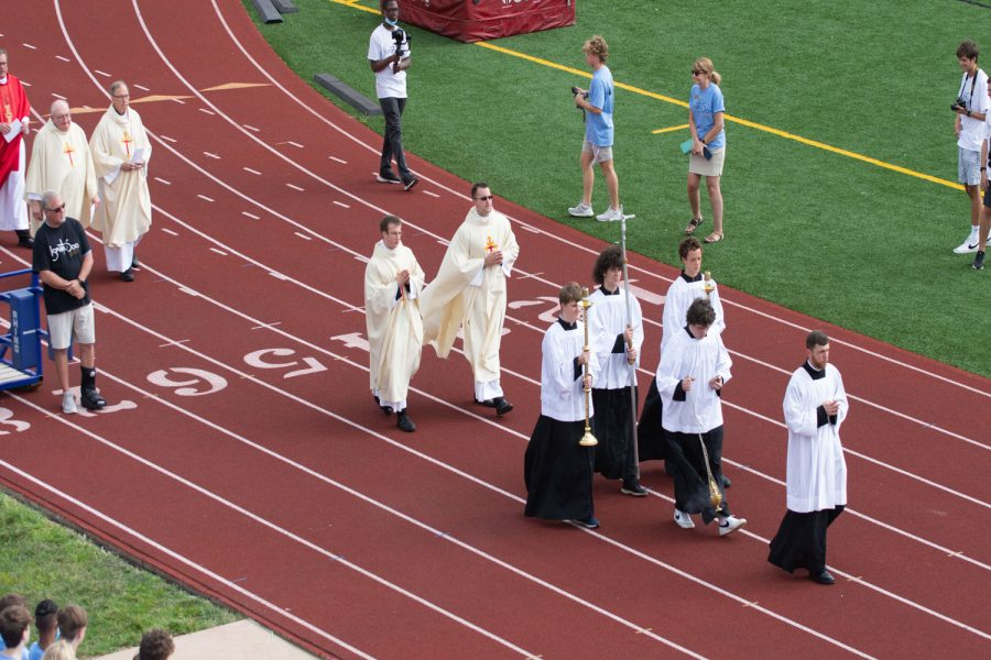 Altar servers lead the clergy procession on the track to start the Mass of the Holy Spirit.